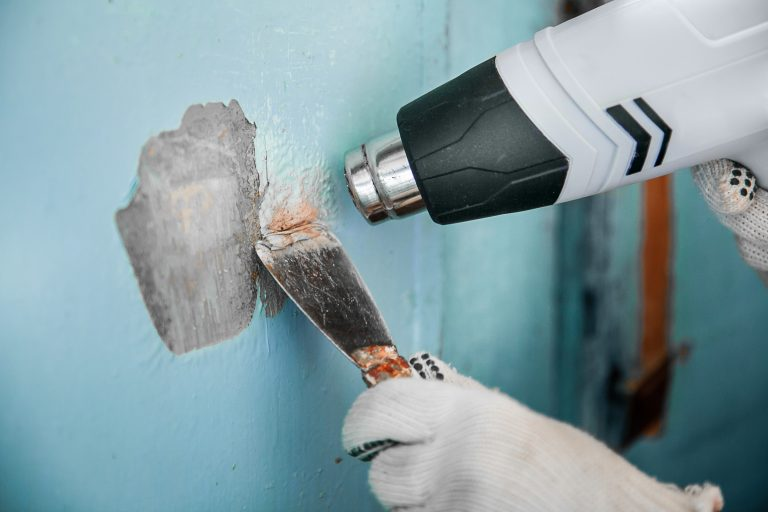 Master removes old blue paint from concrete wall with heat gun and scraper. Closeup