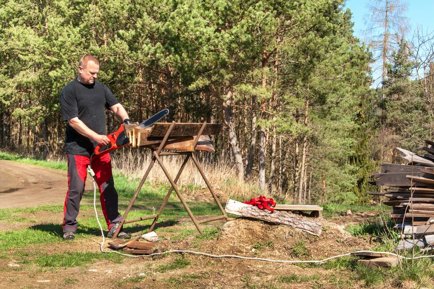 Man cutting with electric chain saw. Work on the farm. Wood preparation for heating. The woodcutter works with the saw.